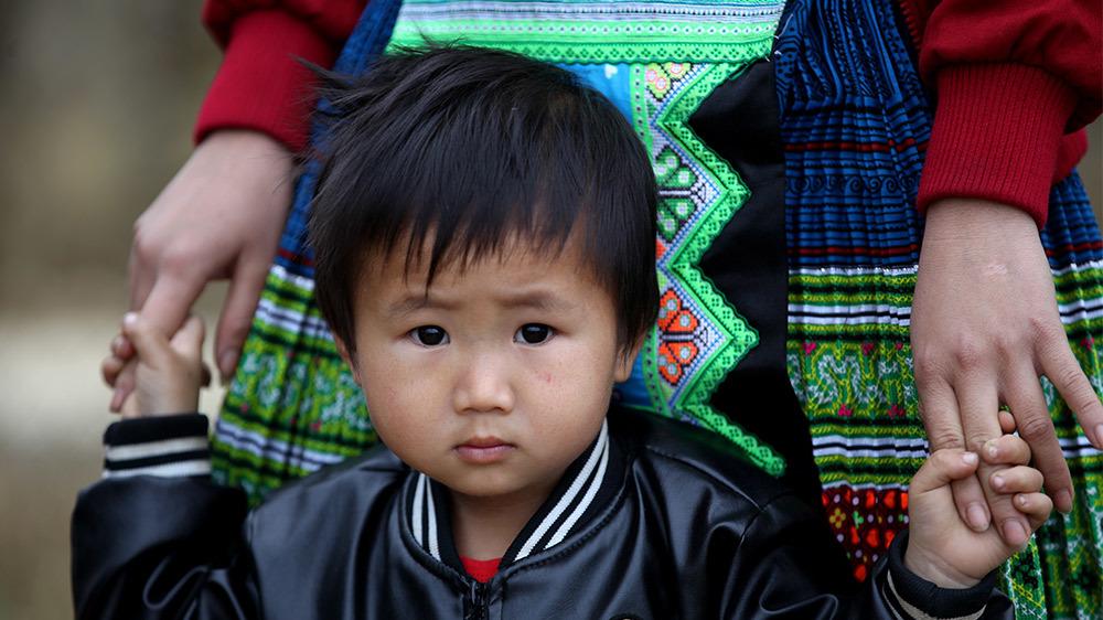 Người phụ nữ H'Mông vừa trông con vừa thi ném pao trên đỉnh Suối Giàng