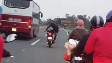 Thanh niên vừa đi xe máy vừa tập thể dục trên quốc lộ