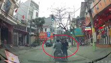 Hai người đàn ông đứng giữa phố nói chuyện mặc ô tô bấm còi inh ỏi