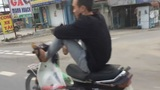 Chàng trai điều khiển xe máy bằng chân trên đường quốc lộ