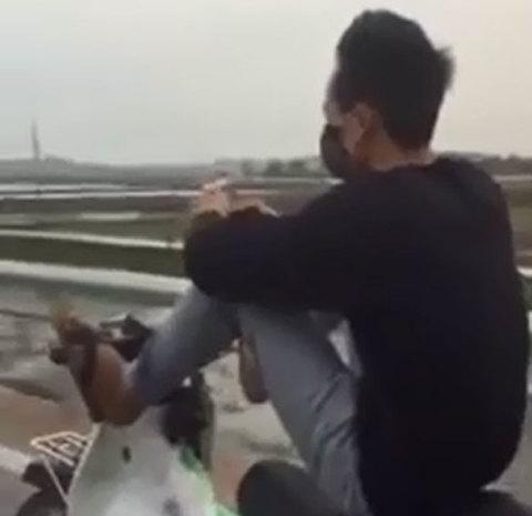Nam thanh niên không mũ bảo hiểm, vừa lái xe bằng chân vừa bấm điện thoại