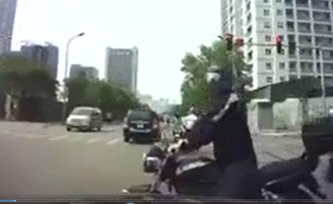 Chen ngang trước mũi ô tô, người đi môtô đưa kí hiệu lạ với tài xế