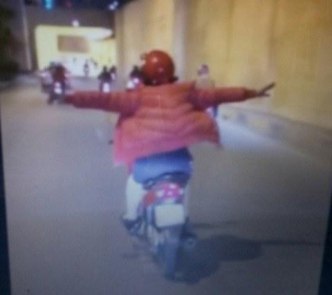 Người phụ nữ lái xe máy buông cả 2 tay