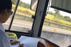 Tài xế xe khách vừa lái xe vừa ghi sổ sách