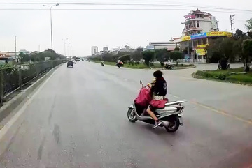 Nữ 'ninja' buông tay lái cởi áo mưa dù đang chở con nhỏ