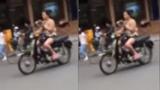 Cô gái vừa đi xe máy vừa vô tư đọc sách, nghe nhạc