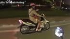 Cô gái liều lĩnh, vừa chở con vừa bấm điện thoại khi đi xe máy