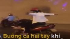 Người phụ nữ gác chân, buông cả hai tay khi đang chạy xe máy