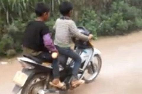 Hai cậu bé vùng cao phối hợp nhịp nhàng giúp nhau đi xe máy
