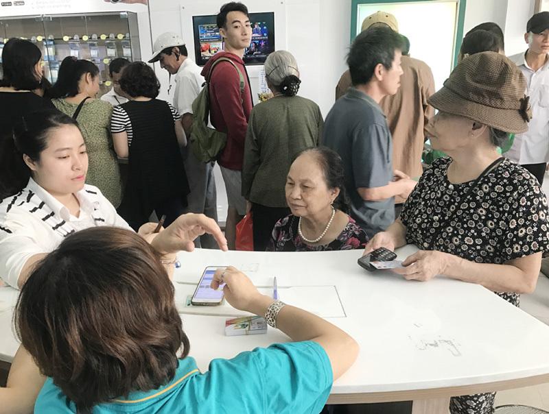 Lùi thời hạn khóa máy: Phòng giao dịch kín người chụp ảnh chân dung