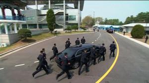 Hình ảnh 12 vệ sĩ vây kín chạy theo xe chở Kim Jong Un đi ăn trưa
