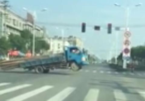 Chiếc xe tải khổ sở nhích từng chút một qua ngã tư bằng hai bánh sau