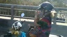 Nữ 'ninja' lái xe máy buông 2 tay, châm thuốc lá hút trên cầu
