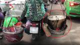 Người phụ nữ vô tư gánh bếp than và nồi nước sôi đi xe máy trên phố