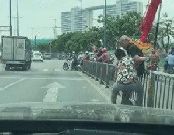 Thanh niên dừng xe, bế cụ già qua dải phân cách tránh nắng