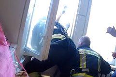 Xem lính cứu hỏa nhoài người qua cửa sổ 'hứng' nạn nhân