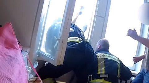 Lính cứu hỏa nhoài người qua cửa sổ hứng nạn nhân ngã từ trên cao