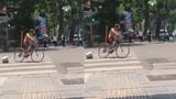 Người đàn ông cởi trần đạp xe chạy vòng quanh ngã tư giữa trời nắng