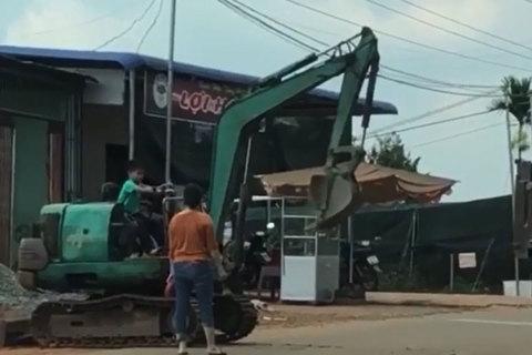 Người phụ nữ thản nhiên để bé trai lái máy xúc sát đường đông