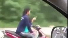 Người phụ nữ chở trẻ em, buông 2 tay để sử dụng điện thoại