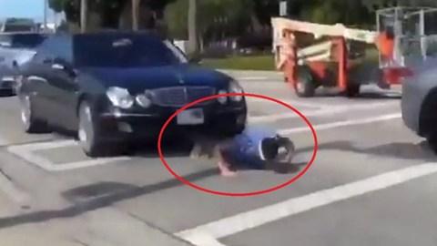 Thanh niên liều chết chui gầm ô tô, chống đẩy giữa phố đông