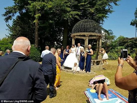 Cô gái tắm nắng giữa công viên mặc cô dâu, chú rể chụp ảnh bên cạnh