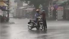 Xúc động hình ảnh người cha cởi áo mưa mặc cho con trai
