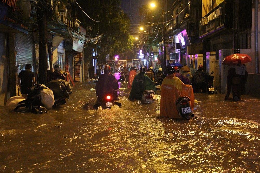 Người Hà Nội đội mưa sầm sập, rùng mình lội nước ngập rác về nhà
