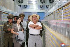 Vợ Kim Jong Un tươi tắn cầm áo khoác cho chồng