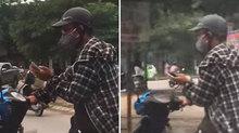 Thanh niên vừa lái xe máy vừa chơi game trên phố đông người