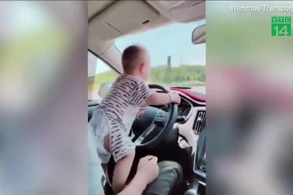Cậu bé còn đang quấn tã lái ô tô chạy băng băng trên đường