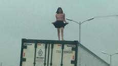 Người phụ nữ váy ngắn nhảy múa trên nóc xe container
