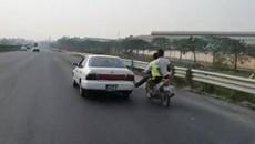 Thanh niên đi xe máy dùng chân không đẩy ô tô chạy băng băng trên cao tốc