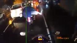 Tà áo mưa cuốn bánh xe, người phụ nữ đi xe máy bị kéo ngã