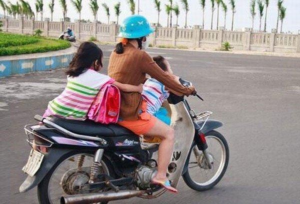 Bà mẹ 1 tay lái xe máy, 1 tay ôm con bú trên đường