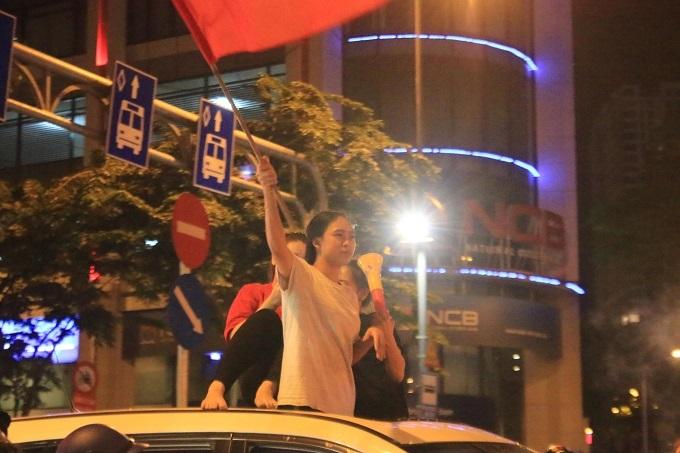Nữ cổ động viên ngồi nóc ô tô, cầm cờ vẫy chào mừng chiến thắng của đội tuyển Việt Nam.