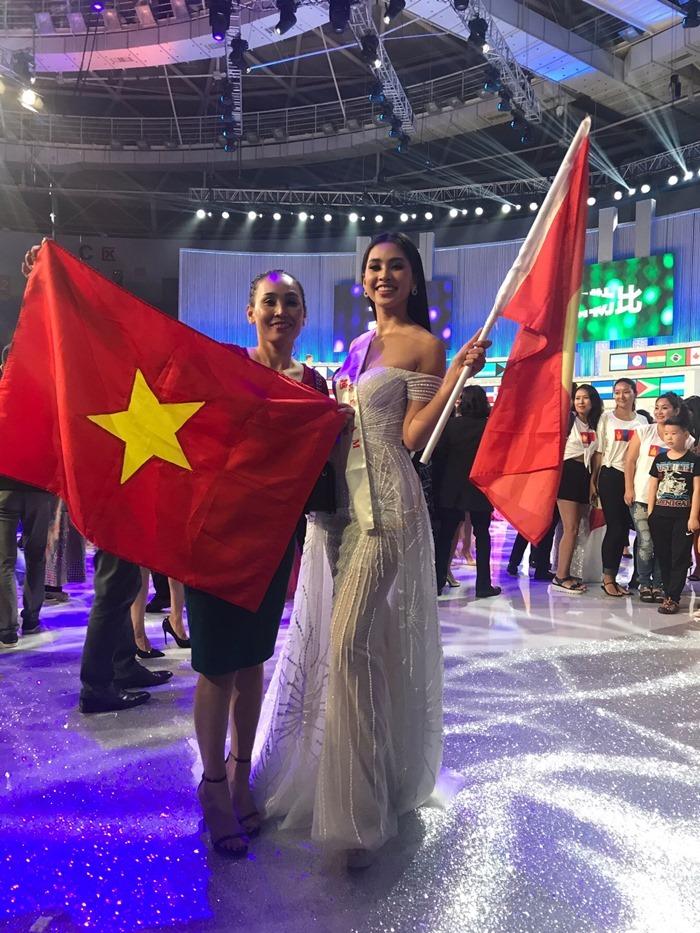 Tiểu Vy ôm mẹ cùng quốc kỳ ghi lại kỷ niệm tại Hoa hậu Thế giới