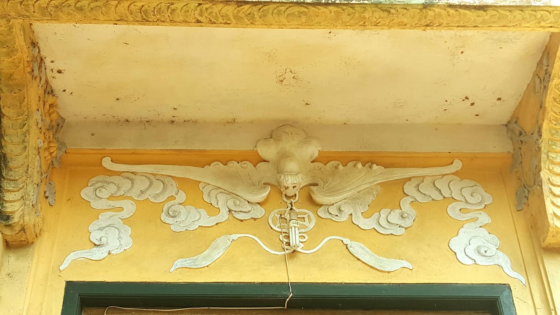 Phía ngoài cửa chính là phù điêu hình con dơi ngậm đồng tiền.Hình ảnh này mang ý nghĩa