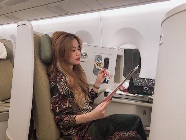 """Hoàng Thùy Linh vừa nhâm nhi rượu vừa dành thời gian để đọc sách trên máy bay. Nữ ca sĩ chia sẻ: """"Có một cuốn sách đọc mãi không xong chỉ tại chị Huệ thi thoảng lại quay đây mẹ chụp hình, quay đây mẹ tâm sự tình yêu, quay đây con xem hình bà này già hơn mẹ đúng không hả""""."""