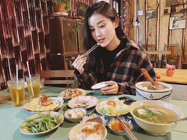 """Á hậu Huyền My ngồi ăn nhưng không quên tạo dáng chụp hình """"sống ảo"""". Cô tự hỏi: """"Được ăn mà sao mặt buồn thế hả Mỳ?""""."""