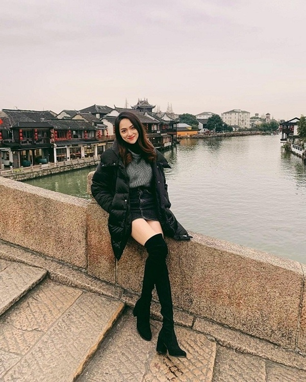 """Hương Giang Idol diện trang phục theo style """"trên đông dưới hè"""" khi đến thăm Phượng Hoàng cổ trấn ở Trung Quốc."""