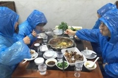 Lý do khiến 4 cô gái trẻ vừa mặc áo mưa vừa xì xụp ăn lẩu