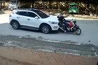 Dừng chờ đèn đỏ, hai mẹ con đi xe máy bất ngờ bị ô tô tông ngã
