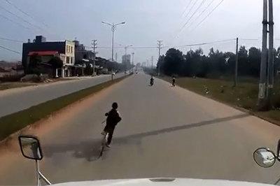 Nam sinh đi xe đạp lạng lách trước mũi xe container