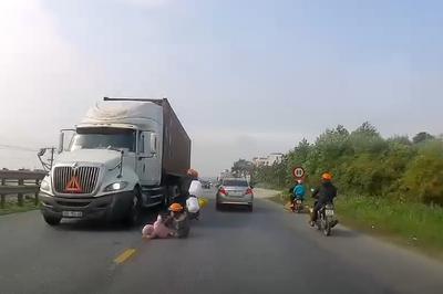 Nghẹt thở giây phút hai mẹ con ngã sát bánh xe container đang lao