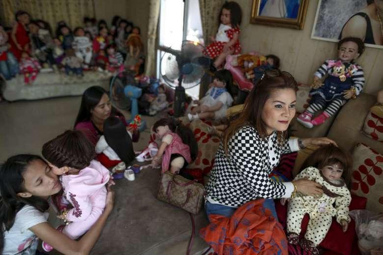 Những người mộ đạo chơi với búp bê trong một ngôi nhà ở Nonthaburi, Thái Lan. Ảnh: Reuters