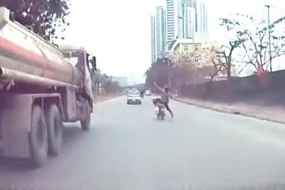 Vừa đi xe máy vừa dùng điện thoại, thanh niên suýt ngã vào xe bồn