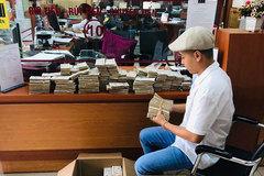 Anh chàng mang 100.000 tờ tiền lẻ 2.000 đồng xếp kín 3 thùng gửi tiết kiệm