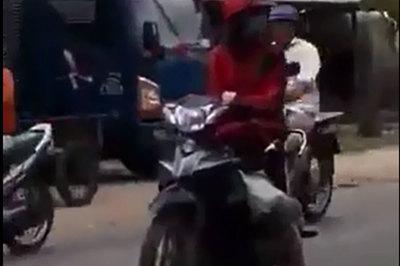 Bất chấp nguy hiểm, cô gái thản nhiên dừng xe máy giữa đường đông người qua lại