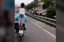 Để con đứng lên yên xe đầu không đội nón bảo hiểm, người cha vẫn chạy xe vèo vèo trên đường gây bức xúc